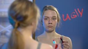 Palabra infeliz fea por la barra de labios en el espejo, inseguridades de la escritura del adolescente de la pubertad almacen de video