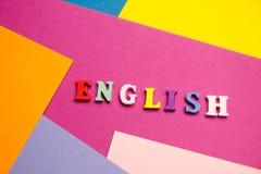 Palabra inglesa compuesta de letras de madera del ABC del bloque colorido del alfabeto, espacio de la copia para el texto del anu Foto de archivo libre de regalías