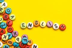 Palabra inglesa compuesta de letras de madera del ABC del bloque colorido del alfabeto, espacio de la copia para el texto del anu Imágenes de archivo libres de regalías
