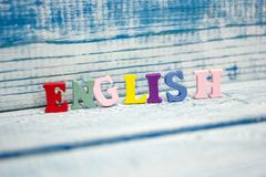 Palabra inglesa compuesta de letras de madera del ABC del bloque colorido del alfabeto, espacio de la copia para el texto del anu Fotos de archivo libres de regalías
