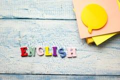 Palabra inglesa compuesta de letras de madera del ABC del bloque colorido del alfabeto, espacio de la copia para el texto del anu Fotografía de archivo libre de regalías