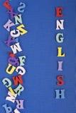 Palabra inglesa en el fondo azul compuesto de letras de madera del ABC del bloque colorido del alfabeto, espacio de la copia para Foto de archivo