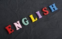 Palabra inglesa en el fondo negro compuesto de letras de madera del ABC del bloque colorido del alfabeto, espacio del tablero de  Imágenes de archivo libres de regalías
