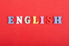 Palabra inglesa en el fondo rojo compuesto de letras de madera del ABC del bloque colorido del alfabeto, espacio de la copia para Fotos de archivo libres de regalías
