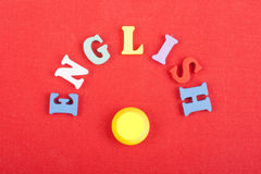 Palabra inglesa en el fondo rojo compuesto de letras de madera del ABC del bloque colorido del alfabeto, espacio de la copia para Imagenes de archivo