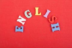 Palabra inglesa en el fondo rojo compuesto de letras de madera del ABC del bloque colorido del alfabeto, espacio de la copia para Foto de archivo libre de regalías
