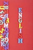 Palabra inglesa en el fondo rojo compuesto de letras de madera del ABC del bloque colorido del alfabeto, espacio de la copia para Fotos de archivo