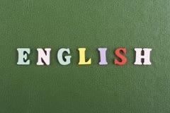 Palabra inglesa en el fondo verde compuesto de letras de madera del ABC del bloque colorido del alfabeto, espacio de la copia par Foto de archivo