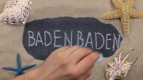 Palabra manuscrita BADEN BADEN, escrito en tiza, entre conchas marinas y estrellas Visión superior almacen de metraje de vídeo