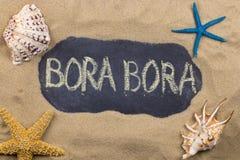 Palabra manuscrita BORA BORA escrito en tiza, entre conchas marinas y estrellas de mar fotografía de archivo