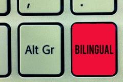 Palabra que escribe al bilingüe del texto Concepto del negocio para hablar dos idiomas con fluidez o más trabajo como traductor K foto de archivo