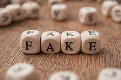 palabra que forma en letras de madera en el fondo de madera del escritorio - falsificación fotografía de archivo libre de regalías