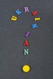 Palabra UCRANIANA en el fondo negro compuesto de letras de madera del ABC del bloque colorido del alfabeto, espacio del tablero d Fotos de archivo libres de regalías