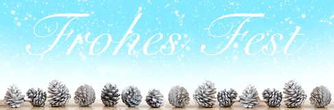 Palabras alemanas para la Feliz Navidad con los pinecones blancos en b nevoso Fotos de archivo