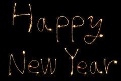 Palabras ardientes de la Feliz Año Nuevo del palillo y de la escritura de la bengala Imagenes de archivo