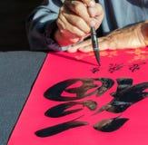 Palabras de la escritura del calígrafo en próspero de papel en palabra china Fotografía de archivo libre de regalías