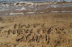 Palabras de la Feliz Año Nuevo 2014 escritas en arena Foto de archivo