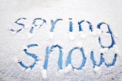 Palabras de la NIEVE de la PRIMAVERA escritas en la nieve en un coche azul Fotografía de archivo libre de regalías