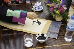 Palabras de la pintura del calígrafo en el papel La caligrafía es una cultura tradicional en Año Nuevo lunar del este Foco en el  Imagen de archivo