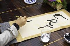 Palabras de la pintura del calígrafo en el papel La caligrafía es una cultura tradicional en Año Nuevo lunar del este Foco en el  Fotografía de archivo