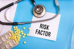 Palabras del factor de riesgo escritas en carpeta azul médica imagenes de archivo