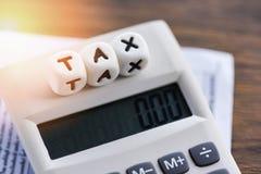 Palabras del impuesto en la calculadora en las finanzas de papel de la cuenta de la factura para el cálculo del impuesto del tiem imágenes de archivo libres de regalías