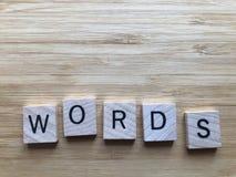 Palabras en las letras de madera, aisladas en fondo anaranjado foto de archivo