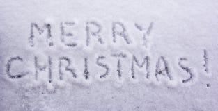 Palabras escritas Feliz Navidad en un fondo nevoso blanco Imágenes de archivo libres de regalías