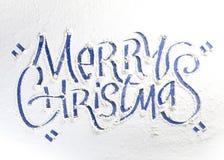 Palabras escritas Feliz Navidad en una nieve imagenes de archivo