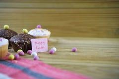 Palabras felices de Pascua con las mini decoraciones de las tortas del chocolate y del huevo de Pascua Imagen de archivo libre de regalías