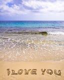Palabras TE AMO escritas en la arena, con las ondas en fondo Imagen de archivo libre de regalías