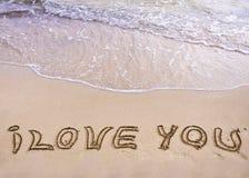 Palabras TE AMO escritas en la arena, con las ondas en fondo Foto de archivo libre de regalías