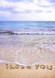 Palabras TE AMO escritas en la arena, con las ondas en fondo Fotos de archivo libres de regalías