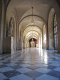 Palace Corridor inside Versailles Castle in France. Sun and lamplight illumine statuary of royalty in a long arched corridor. Palace of Versailles in France Royalty Free Stock Image