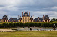 The Palace of Fontainebleau. Fontainebleau,France- June 19, 2011: People walking in a beautiful courtyard located in front of a part of The Palace of Royalty Free Stock Photos