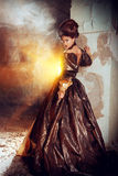 Palace ruine. Art Fashion. Beautiful young woman in elegant historical dress and with barocco updo hairstyle posing in the ruins of the castle. Renaissance Stock Image