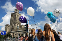 Palace of science and culture in Warsaw and girls with baloons. Girls with balloons walking on the street of Warsaw royalty free stock photo
