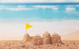 The palaces of sand, yellow flag on beach. The palaces of sand, a yellow flag on the beach Royalty Free Stock Photo