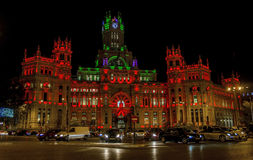 Palacio de Comunicaciones building at night with red lights and ribbon symbolizing AIDS international day Royalty Free Stock Image
