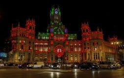 Palacio de Comunicaciones byggnad på natten med röda ljus och bandet som symboliserar HJÄLPMEDELinternationaldag Royaltyfri Bild