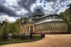 Palacio de cristal with dramatic clouds. The crystal palace in the Retiro Park in Madrid (Spain royalty free stock photo
