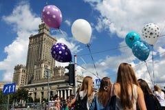 Palacio de la ciencia y cultura en Varsovia y muchachas con los baloons Foto de archivo libre de regalías