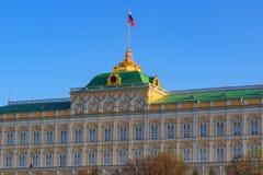 Palacio magnífico del Kremlin con la bandera de la Federación Rusa en el primer del tejado en un fondo del cielo azul por mañana  Foto de archivo libre de regalías