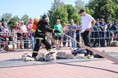 Palacz trzyma pożarniczego węża elastycznego przy pożarniczą sport rywalizacją w fireproof kostiumu i hełmie Minsk, Białoruś, 08  obrazy stock