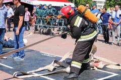 Palacz trzyma pożarniczego węża elastycznego przy pożarniczą sport rywalizacją w fireproof kostiumu i hełmie Minsk, Białoruś, 08  fotografia stock