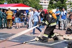 Palacz trzyma pożarniczego węża elastycznego przy pożarniczą sport rywalizacją w fireproof kostiumu i hełmie Minsk, Białoruś, 08  obraz stock