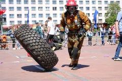 Palacz w fireproof kostiumu biega wielki gumowego i obraca toczy wewnątrz pożarniczego boju rywalizację, Białoruś, Minsk, 08 08 2 zdjęcia stock