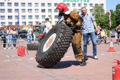 Palacz w fireproof kostiumu biega wielki gumowego i obraca toczy wewnątrz pożarniczego boju rywalizację, Białoruś, Minsk, 08 08 2 obrazy stock