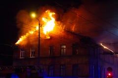 Palacze kierują wodnego strumienia na palenie domu budujący w pełnej płomiennej jatce i strażaka boju dostawać kontrola fl, fotografia stock