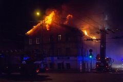 Palacze kierują wodnego strumienia na palenie domu budujący w pełnej płomiennej jatce i strażaka boju dostawać kontrola fl, obraz stock